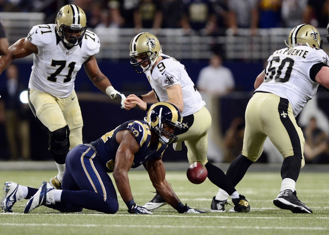 Dec 15, 2013; St. Louis, MO, USA; St. Louis Rams defensive end Robert Quinn (94) forces a fumble and recovers the ball from New Orleans Saints quarterback Drew Brees (9) during the second half at the Edward Jones Dome. The Rams defeated the Saints 27-16. Mandatory Credit: Jeff Curry-USA TODAY Sports