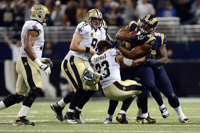 Dec 15, 2013; St. Louis, MO, USA; St. Louis Rams defensive end Robert Quinn (94) is tackled by New Orleans Saints running back Pierre Thomas (23) after causing a fumble and recovering the ball from quarterback Drew Brees (9) during the second half at the Edward Jones Dome. The Rams defeated the Saints 27-16. Mandatory Credit: Jeff Curry-USA TODAY Sports