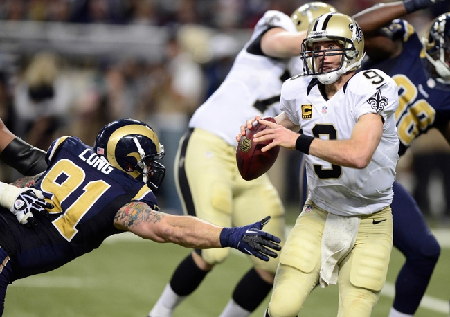 Dec 15, 2013; St. Louis, MO, USA; New Orleans Saints quarterback Drew Brees (9) looks to pass as St. Louis Rams defensive end Chris Long (91) defends during the second half at the Edward Jones Dome. The Rams defeated the Saints 27-16. Mandatory Credit: Jeff Curry-USA TODAY Sports
