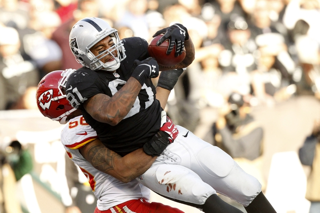Dec 15, 2013; Oakland, CA, USA; Oakland Raiders tight end Mychal Rivera (81) catches a touchdown pass over Kansas City Chiefs inside linebacker Derrick Johnson (56) in the third quarter at O.co Coliseum. The Chiefs defeated the Raiders 56-31. Mandatory Credit: Cary Edmondson-USA TODAY Sports