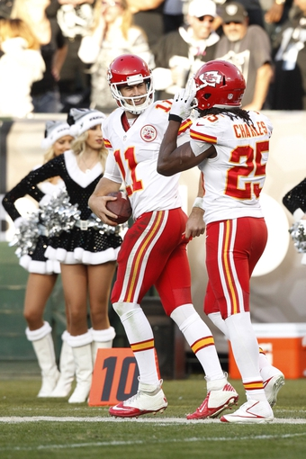 Dec 15, 2013; Oakland, CA, USA; Kansas City Chiefs running back Jamaal Charles (25) is congratulated by quarterback Alex Smith (11) after catching a 71 yard touchdown pass against the Oakland Raiders in the third quarter at O.co Coliseum. The Chiefs defeated the Raiders 56-31. Mandatory Credit: Cary Edmondson-USA TODAY Sports