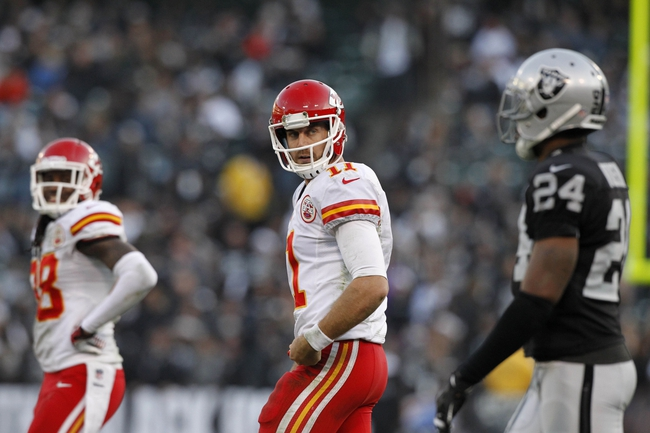 Dec 15, 2013; Oakland, CA, USA; Kansas City Chiefs quarterback Alex Smith (11) looks back towards Oakland Raiders free safety Charles Woodson (24) after running the ball in the fourth quarter at O.co Coliseum. The Chiefs defeated the Raiders 56-31. Mandatory Credit: Cary Edmondson-USA TODAY Sports