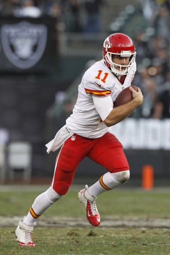 Dec 15, 2013; Oakland, CA, USA; Kansas City Chiefs quarterback Alex Smith (11) runs the ball against the Oakland Raiders in the fourth quarter at O.co Coliseum. The Chiefs defeated the Raiders 56-31. Mandatory Credit: Cary Edmondson-USA TODAY Sports