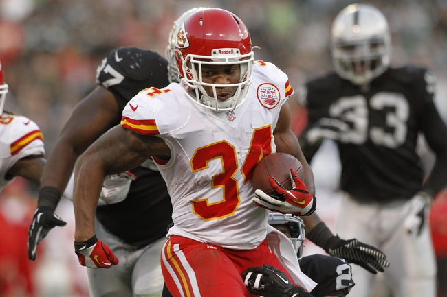 Dec 15, 2013; Oakland, CA, USA; Kansas City Chiefs running back Knile Davis (34) runs the ball against the Oakland Raiders in the fourth quarter at O.co Coliseum. The Chiefs defeated the Raiders 56-31. Mandatory Credit: Cary Edmondson-USA TODAY Sports