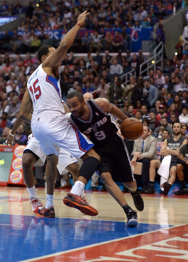 Dec 16, 2013; Los Angeles, CA, USA; San Antonio Spurs guard Tony Parker (9) is defended by Los Angeles Clippers center Ryan Hollins (15) at Staples Center. Mandatory Credit: Kirby Lee-USA TODAY Sports