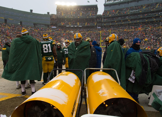 Dec 8, 2013; Green Bay, WI, USA; The Green Bay Packers huddle around heaters during the game against the Atlanta Falcons at Lambeau Field.  Green Bay won 22-21.  Mandatory Credit: Jeff Hanisch-USA TODAY Sports