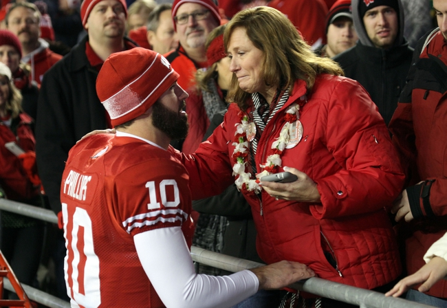 Nov 30, 2013; Madison, WI, USA; Wisconsin Badgers quarterback Curt Phillips (10) is consoled after his team's defeat to the Penn State Nittany Lions at Camp Randall Stadium. Penn State defeated Wisconsin 31-24. Mandatory Credit: Mary Langenfeld-USA TODAY Sports