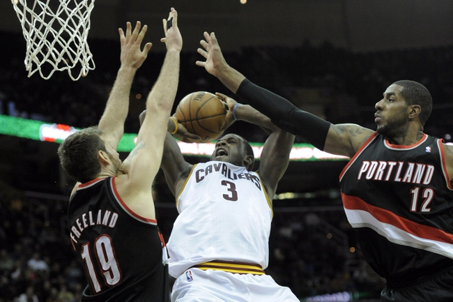 Dec 17, 2013; Cleveland, OH, USA; Cleveland Cavaliers shooting guard Dion Waiters (3) drives between Portland Trail Blazers power forward LaMarcus Aldridge (12) and center Joel Freeland (19) in the fourth quarter at Quicken Loans Arena. Mandatory Credit: David Richard-USA TODAY Sports