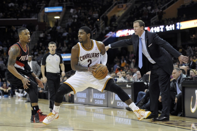 Dec 17, 2013; Cleveland, OH, USA; Portland Trail Blazers head coach Terry Stotts (right) watches as point guard Damian Lillard (left) guards Cleveland Cavaliers point guard Kyrie Irving (2) in the fourth quarter at Quicken Loans Arena. Mandatory Credit: David Richard-USA TODAY Sports
