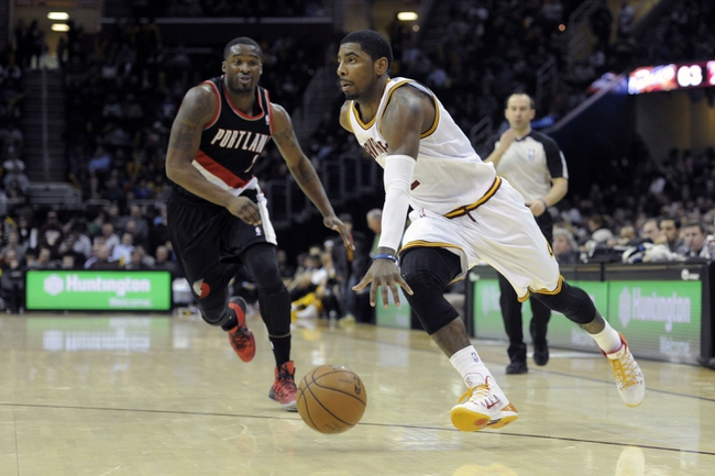Dec 17, 2013; Cleveland, OH, USA; Cleveland Cavaliers point guard Kyrie Irving (right) drives against Portland Trail Blazers shooting guard Wesley Matthews (2) in the third quarter at Quicken Loans Arena. Mandatory Credit: David Richard-USA TODAY Sports