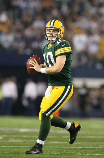 Dec 15, 2013; Arlington, TX, USA; Green Bay Packers quarterback Matt Flynn (10) scrambles out of the pocket in the fourth quarter against the Dallas Cowboys at AT&T Stadium. The Packers beat the Cowboys 37-36. Mandatory Credit: Matthew Emmons-USA TODAY Sports
