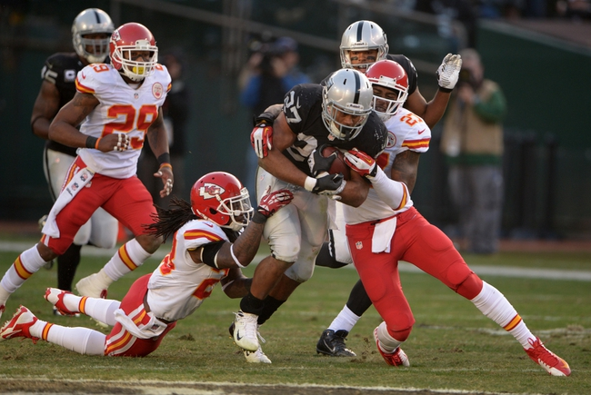 Dec 15, 2013; Oakland, CA, USA; Oakland Raiders running back Rashad Jennings (27) is tackled by Kansas City Chiefs safety Kendrick Lewis (23) and cornerback Sean Smith (27) at O.co Coliseum. The Chiefs defeated the Raiders 56-31. Mandatory Credit: Kirby Lee-USA TODAY Sports