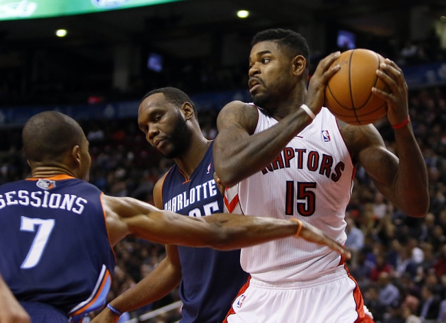 Dec 18, 2013; Toronto, Ontario, CAN; Toronto Raptors forward-center Amir Johnson (15) comes down with a rebound against Charlotte Bobcats guard Ramon Sessions (7) and center Al Jefferson (25) during the first half at the Air Canada Centre. Mandatory Credit: John E. Sokolowski-USA TODAY Sports