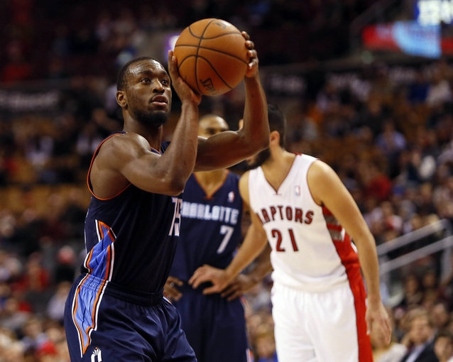 Dec 18, 2013; Toronto, Ontario, CAN; Charlotte Bobcats guard Kemba Walker (15) goes to throw a free throw against the Toronto Raptors at the Air Canada Centre. Charlotte defeated Toronto 104-102 in overtime. Mandatory Credit: John E. Sokolowski-USA TODAY Sports