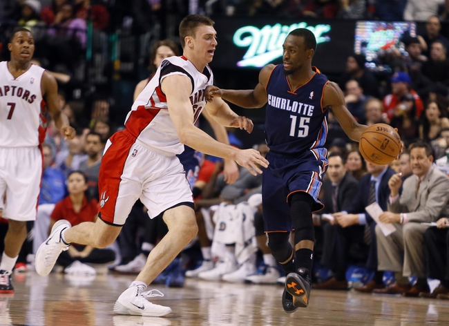Dec 18, 2013; Toronto, Ontario, CAN; Charlotte Bobcats guard Kemba Walker (15) goes to pass as Toronto Raptors forward Tyler Hansbrough (50) defends at the Air Canada Centre. Charlotte defeated Toronto 104-102 in overtime. Mandatory Credit: John E. Sokolowski-USA TODAY Sports