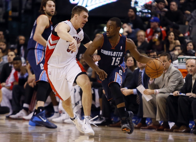 Dec 18, 2013; Toronto, Ontario, CAN; Charlotte Bobcats guard Kemba Walker (15) dribbles the ball as Toronto Raptors forward Tyler Hansbrough (50) defends at the Air Canada Centre. Charlotte defeated Toronto 104-102 in overtime. Mandatory Credit: John E. Sokolowski-USA TODAY Sports