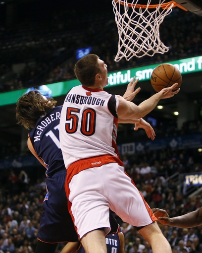 Dec 18, 2013; Toronto, Ontario, CAN; Toronto Raptors forward Tyler Hansbrough (50) goes to make a lay up as Charlotte Bobcats forward Josh McRoberts (11) defends at the Air Canada Centre. Charlotte defeated Toronto 104-102 in overtime. Mandatory Credit: John E. Sokolowski-USA TODAY Sports