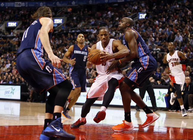 Dec 18, 2013; Toronto, Ontario, CAN; Toronto Raptors guard DeMar DeRozan (10) tries to get past Charlotte Bobcats forward Josh McRoberts (11) and Charlotte Bobcats forward Anthony Tolliver (right) at the Air Canada Centre. Charlotte defeated Toronto 104-102 in overtime. Mandatory Credit: John E. Sokolowski-USA TODAY Sports