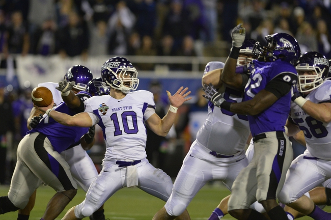 Dec 20, 2013; Salem, VA, USA; Mount Union Purple Raiders quarterback Kevin Burke (10) passes the ball as UW-Whitewater defensive lineman Kevon Clunis (92) pressures in the second quarter at Salem Stadium. Mandatory Credit: Bob Donnan-USA TODAY Sports