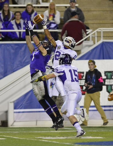 Dec 20, 2013; Salem, VA, USA; UW-Whitewater wide receiver Jake Kumerow (1) catches a pass as Mount Union Purple Raiders defensive backs Isaiah Chambers (23) and Mike Maier (15) defend in the fourth quarter. UW-Whitewater defeated Mount Union Purple Raiders 52-14 at Salem Stadium. Mandatory Credit: Bob Donnan-USA TODAY Sports