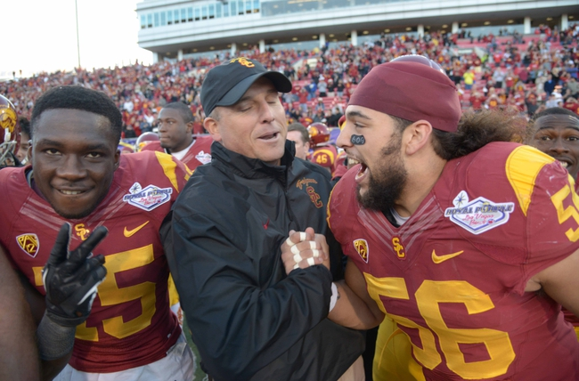 Dec 21, 2013; Las Vegas, NV, USA; Southern California Trojans interim coach Clay Helton (center) celebrates with linebacker Anthony Sarao (56) after the game against the Fresno State Bulldogs in the Las Vegas Bowl at Sam Boyd Stadium. USC defeated Fresno State 45-20. Mandatory Credit: Kirby Lee-USA TODAY Sports