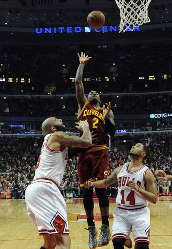 Dec 21, 2013; Chicago, IL, USA; Cleveland Cavaliers point guard Kyrie Irving (2) shoots over Chicago Bulls point guard D.J. Augustin (14) and power forward Carlos Boozer (5) during the first quarter at the United Center. Mandatory Credit: David Banks-USA TODAY Sports