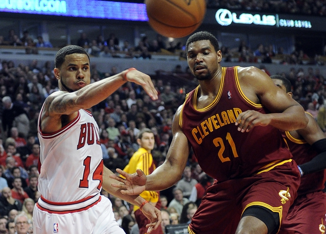 Dec 21, 2013; Chicago, IL, USA;  Chicago Bulls point guard D.J. Augustin (14) passes the ball around Cleveland Cavaliers center Andrew Bynum (21) during the second half at the United Center. T'he Chicago Bulls defeated the Cleveland Cavaliers 100-84. Mandatory Credit: David Banks-USA TODAY Sports