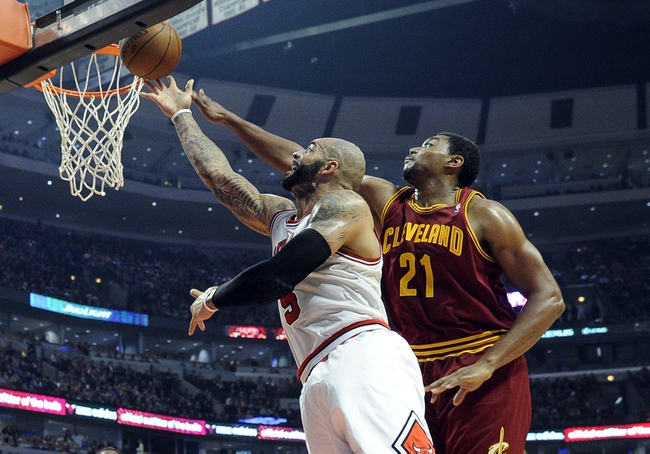 Dec 21, 2013; Chicago, IL, USA; Chicago Bulls power forward Carlos Boozer (5) is defended by Cleveland Cavaliers center Andrew Bynum (21) during the second half at the United Center. T'he Chicago Bulls defeated the Cleveland Cavaliers 100-84. Mandatory Credit: David Banks-USA TODAY Sports