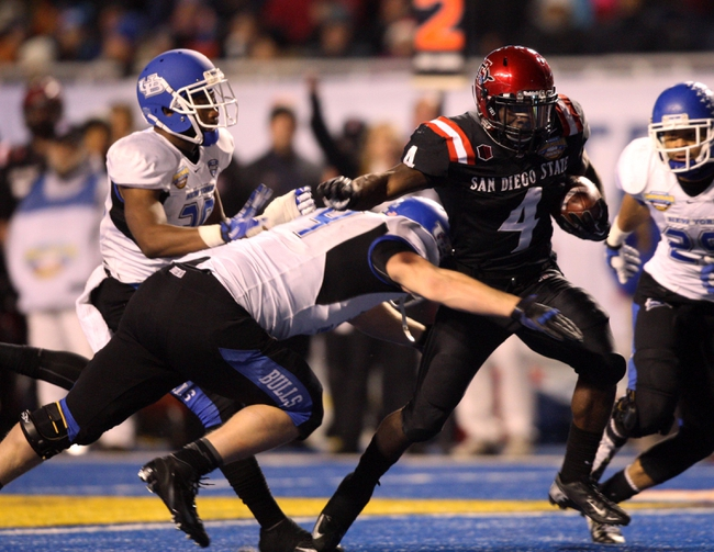 Dec 21, 2013; Boise, ID, USA; San Diego State Aztecs running back Adam Muema (4) runs as Buffalo Bulls defensive back Cortney Lester (4) tries to make the tackle during the second half of the Idaho Potato Bowl at Bronco Stadium. San Diego defeated Buffalo 49-24. Mandatory Credit: Brian Losness-USA TODAY Sports