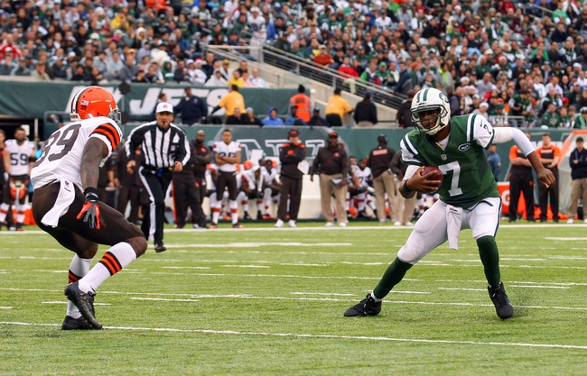 Dec 22, 2013; East Rutherford, NJ, USA; New York Jets quarterback Geno Smith (7) runs with the ball while being chased by Cleveland Browns free safety Tashaun Gipson (39) during the first half at MetLife Stadium. Mandatory Credit: Ed Mulholland-USA TODAY Sports