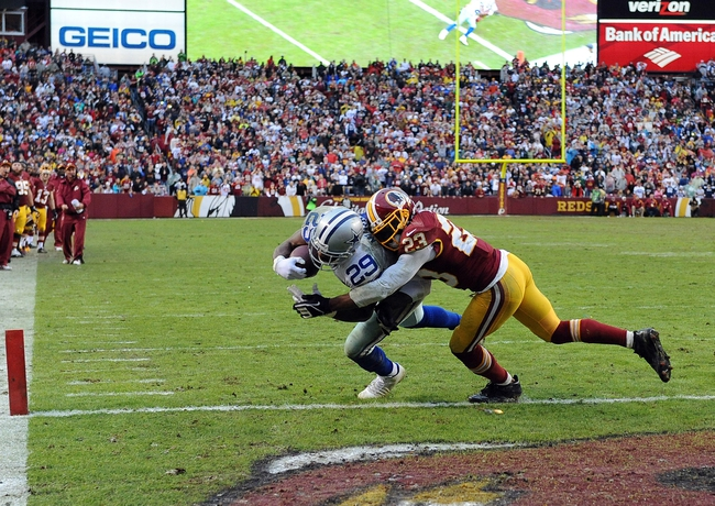 Dec 8, 2013; Landover, MD, USA; Dallas Cowboys running back DeMarco Murray (29) scores a touchdown as Washington Redskins cornerback DeAngelo Hall (23) defends during the fourth quarter at FedEx Field. Mandatory Credit: Brad Mills-USA TODAY Sports