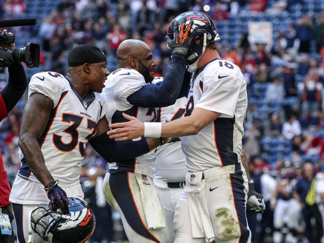 Dec 22, 2013; Houston, TX, USA; Denver Broncos quarterback Peyton Manning (18) is congratulated by teammates after throwing a touchdown during the fourth quarter against the Houston Texans at Reliant Stadium. The touchdown pass set an NFL record for touchdown passes in  a season. Mandatory Credit: Troy Taormina-USA TODAY Sports