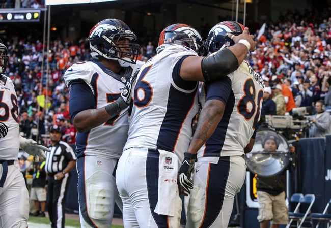 Dec 22, 2013; Houston, TX, USA; Denver Broncos tight end Julius Thomas (80) is congratulated by teammates after scoring a touchdown during the fourth quarter against the Houston Texans at Reliant Stadium. Mandatory Credit: Troy Taormina-USA TODAY Sports