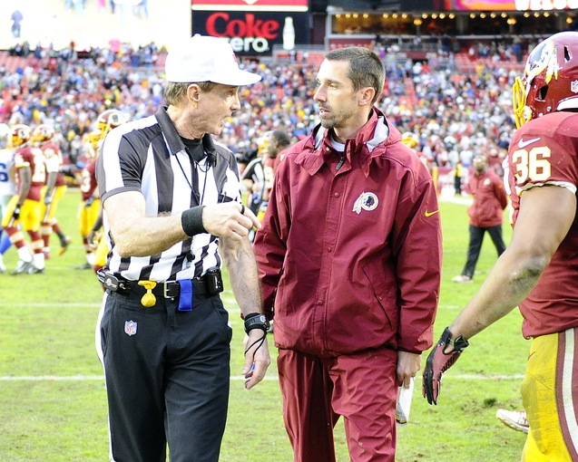Dec 8, 2013; Landover, MD, USA; Washington Redskins offensive coordinator Kyle Shannahan has a discussion with referee Carl Cheffers after the game against the Dallas Cowboys at FedEx Field. Mandatory Credit: Brad Mills-USA TODAY Sports