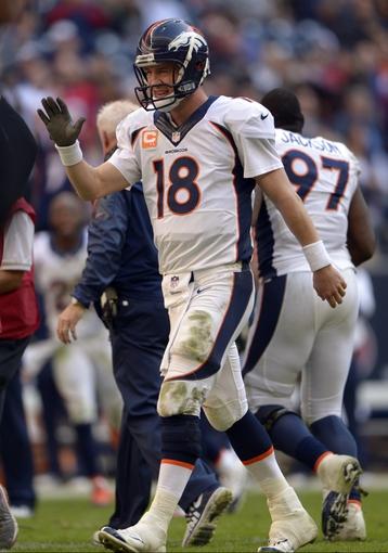 Dec 22, 2013; Houston, TX, USA; Denver Broncos quarterback Peyton Manning (18) celebrates throwing his 51st passing touchdown of the season, setting a single-season record during the second half against the Houston Texans at Reliant Stadium. The Broncos won 37-13. Mandatory Credit: Thomas Campbell-USA TODAY Sports