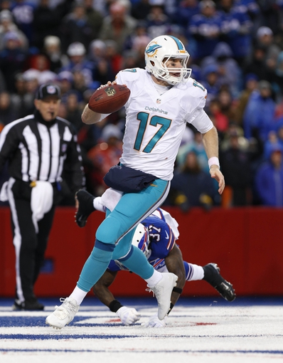 Dec 22, 2013; Orchard Park, NY, USA; Miami Dolphins quarterback Ryan Tannehill (17) breaks a tackle in the end zone by Buffalo Bills defensive back Nickell Robey (37) during the second half at Ralph Wilson Stadium. Bills beat the Dolphins 19-0. Mandatory Credit: Kevin Hoffman-USA TODAY Sports