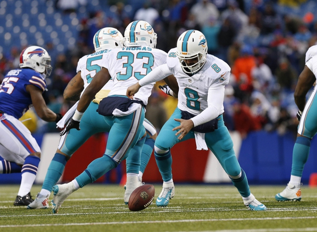 Dec 22, 2013; Orchard Park, NY, USA; Miami Dolphins quarterback Matt Moore (8) fumbles the ball during the second half against the Buffalo Bills at Ralph Wilson Stadium. Bills beat the Dolphins 19-0. Mandatory Credit: Kevin Hoffman-USA TODAY Sports