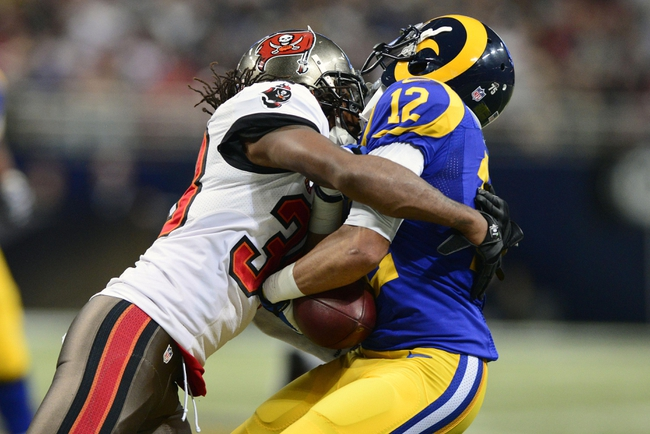 Dec 22, 2013; St. Louis, MO, USA; Tampa Bay Buccaneers free safety Dashon Goldson (38) hits St. Louis Rams wide receiver Stedman Bailey (12) during the second half at the Edward Jones Dome. The Rams defeated the Buccaneers 23-13. Mandatory Credit: Jeff Curry-USA TODAY Sports