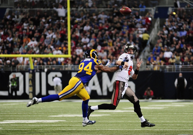 Dec 22, 2013; St. Louis, MO, USA; Tampa Bay Buccaneers quarterback Mike Glennon (8) throws the ball away as he is pressured by St. Louis Rams defensive end Robert Quinn (94) during the second half at the Edward Jones Dome. The Rams defeated the Buccaneers 23-13. Mandatory Credit: Jeff Curry-USA TODAY Sports