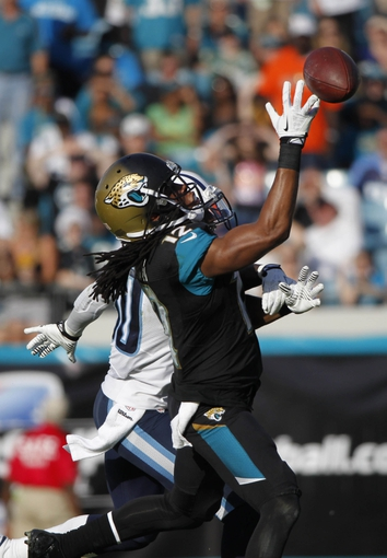 Dec 22, 2013; Jacksonville, FL, USA; Jacksonville Jaguars wide receiver Mike Brown (12) missed the ball as Tennessee Titans cornerback Jason McCourty (30) defends during the second half at EverBank Field. Tennessee Titans defeated the Jacksonville Jaguars 20-16.  Mandatory Credit: Kim Klement-USA TODAY Sports