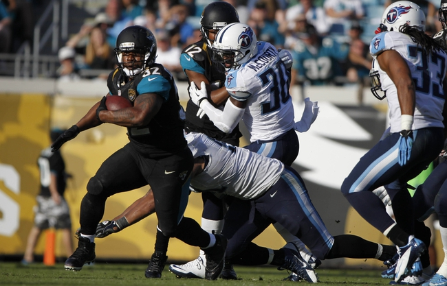 Dec 22, 2013; Jacksonville, FL, USA; Jacksonville Jaguars running back Maurice Jones-Drew (32) runs with the ball against the Tennessee Titans during the second half at EverBank Field. Tennessee Titans defeated the Jacksonville Jaguars 20-16.  Mandatory Credit: Kim Klement-USA TODAY Sports
