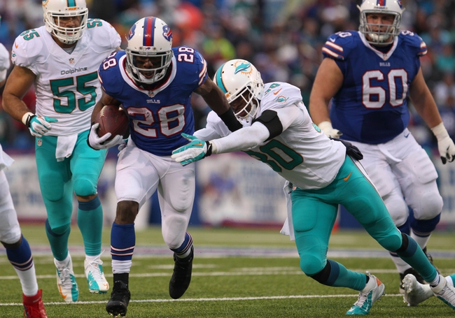 Dec 22, 2013; Orchard Park, NY, USA; Miami Dolphins strong safety Chris Clemons (30) tries to make a tackle on Buffalo Bills running back C.J. Spiller (28) during the second half at Ralph Wilson Stadium. Buffalo beats Miami 19-0.  Mandatory Credit: Timothy T. Ludwig-USA TODAY Sports
