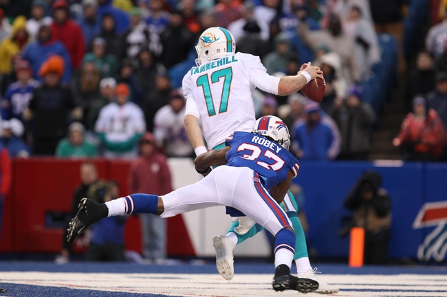 Dec 22, 2013; Orchard Park, NY, USA; Miami Dolphins quarterback Ryan Tannehill (17) avoids a sack by Buffalo Bills defensive back Nickell Robey (37) during the second half at Ralph Wilson Stadium. Buffalo beats Miami 19-0.  Mandatory Credit: Timothy T. Ludwig-USA TODAY Sports