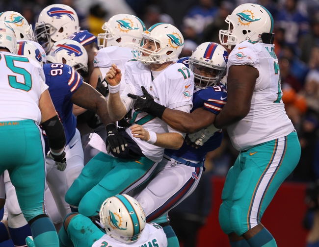 Dec 22, 2013; Orchard Park, NY, USA; Buffalo Bills outside linebacker Jerry Hughes (55) hits Miami Dolphins quarterback Ryan Tannehill (17) after he throws the ball during the second half at Ralph Wilson Stadium. Buffalo beats Miami 19-0.  Mandatory Credit: Timothy T. Ludwig-USA TODAY Sports