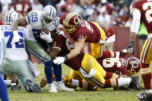 Dec 22, 2013; Landover, MD, USA; Dallas Cowboys running back DeMarco Murray (29) carries the ball as Washington Redskins outside linebacker Ryan Kerrigan (91) dives to make the tackle in the fourth quarter at FedEx Field. The Cowboys won 24-23. Mandatory Credit: Geoff Burke-USA TODAY Sports