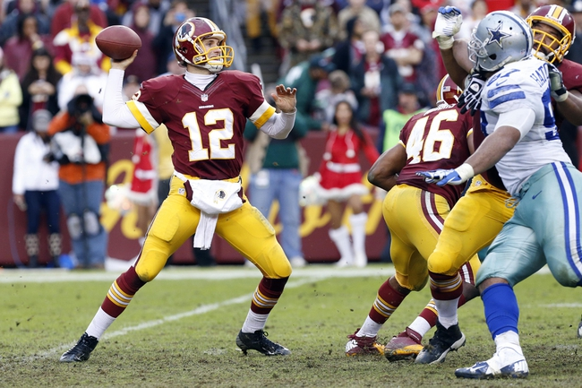 Dec 22, 2013; Landover, MD, USA; Washington Redskins quarterback Kirk Cousins (12) throws the ball as Dallas Cowboys defensive tackle Jason Hatcher (97) chases in the third quarter at FedEx Field. The Cowboys won 24-23. Mandatory Credit: Geoff Burke-USA TODAY Sports