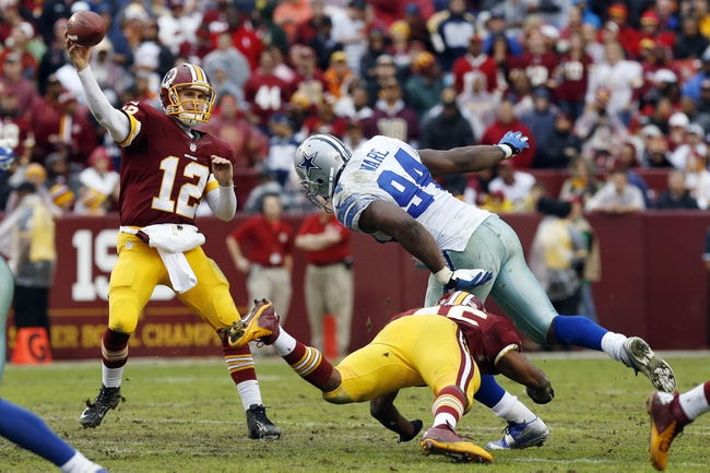 Dec 22, 2013; Landover, MD, USA; Washington Redskins quarterback Kirk Cousins (12) throws the ball as Dallas Cowboys defensive end DeMarcus Ware (94) chases in the third quarter at FedEx Field. The Cowboys won 24-23. Mandatory Credit: Geoff Burke-USA TODAY Sports