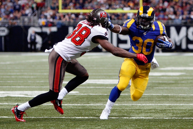 Dec 22, 2013; St. Louis, MO, USA; Tampa Bay Buccaneers free safety Dashon Goldson (38) tries to tackle St. Louis Rams running back Zac Stacy (30) as he carries the ball during a game at the Edward Jones Dome. Mandatory Credit: Scott Kane-USA TODAY Sports
