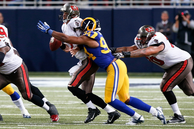 Dec 22, 2013; St. Louis, MO, USA; Tampa Bay Buccaneers quarterback Mike Glennon (8) is sacked during the fourth quarter by St. Louis Rams defensive end Robert Quinn (94) at the Edward Jones Dome. Mandatory Credit: Scott Kane-USA TODAY Sports
