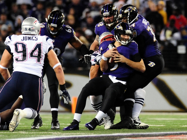 Dec 22, 2013; Baltimore, MD, USA; Baltimore Ravens quarterback Joe Flacco (5) is sacked in the second quarter against the New England Patriots at M&T Bank Stadium. Mandatory Credit: Evan Habeeb-USA TODAY Sports